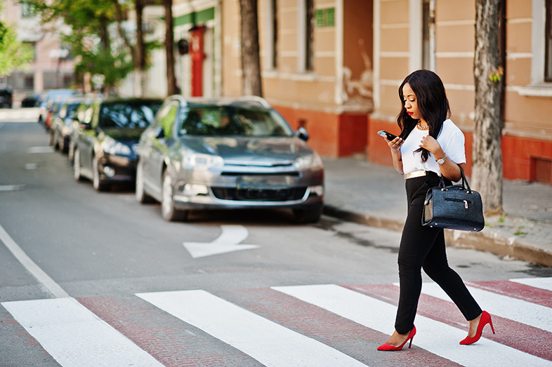 Woman looking down at her phone while crossing a Wisconsin street