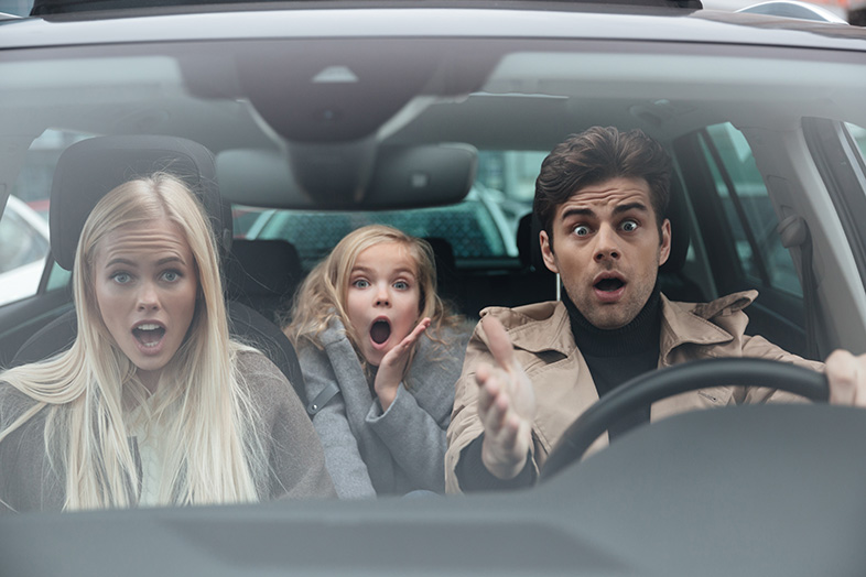 Shocked scared young man sitting in car with family