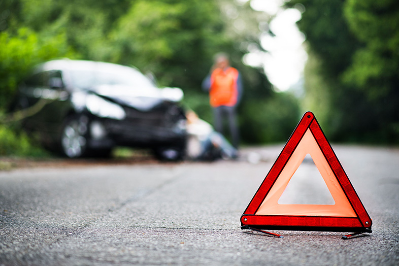 Red emergency triangle on a rural road in front of a car after an accident