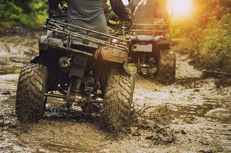 Two ATVs riding through the mud on a Wisconsin ATV trail