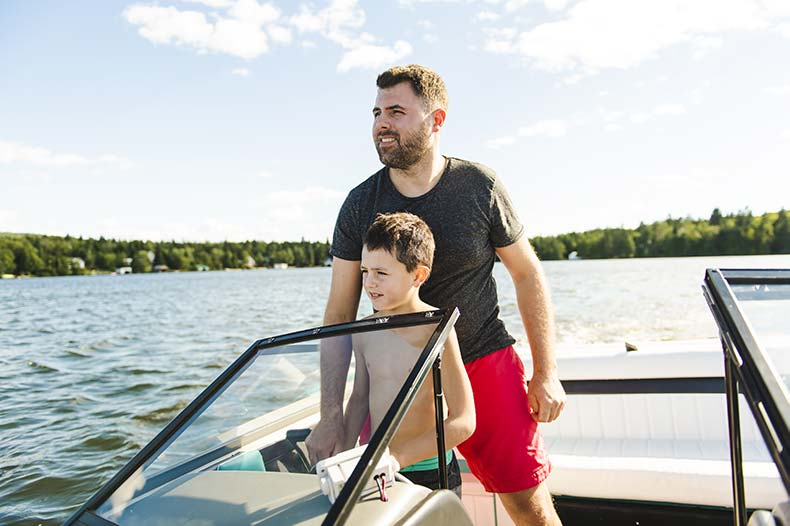 Father teaching his son how to drive a boat on a Wisconsin lake