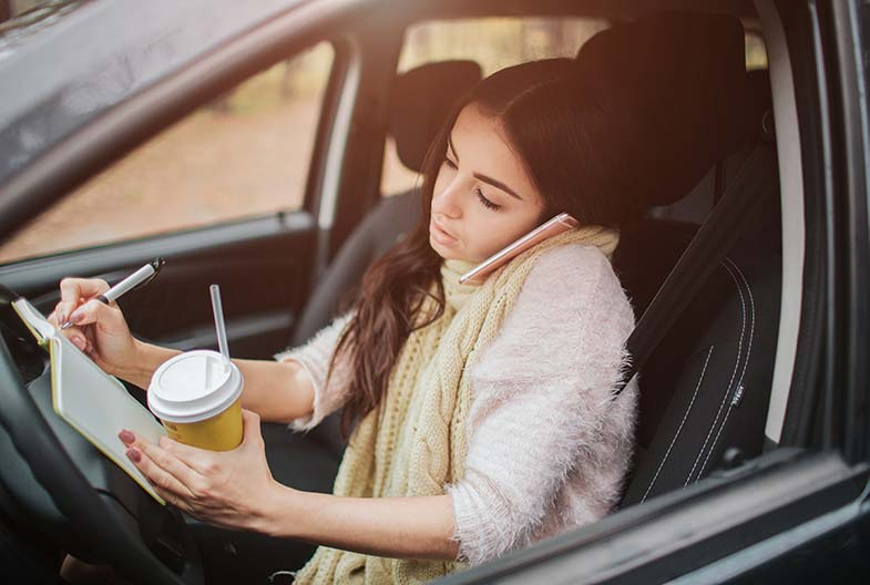Young Wisconsin woman talking on her phone, writing in a notebook, and drinking coffee while driving