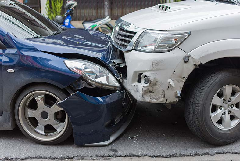 A head-on collision between a blue car and a white car