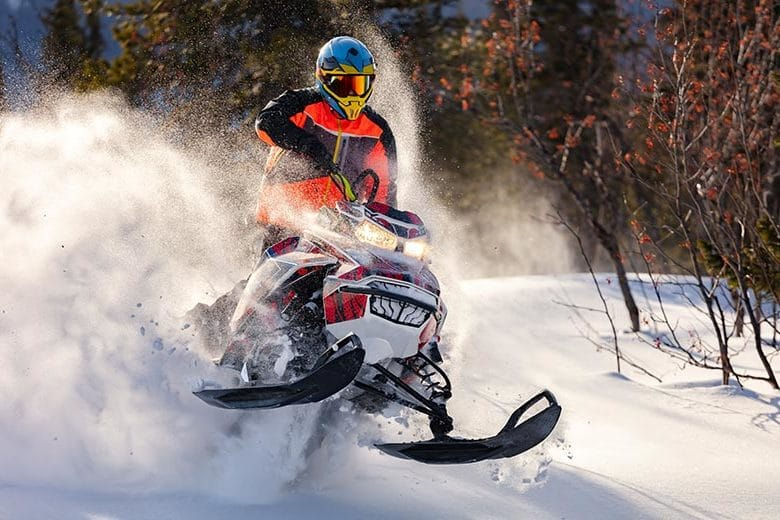 Snowmobile blowing through fresh snow on a Wisconsin trail.