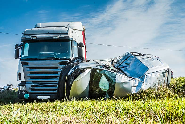 Semi-truck and seriously damaged car on the side of a Wisconsin road following an accident