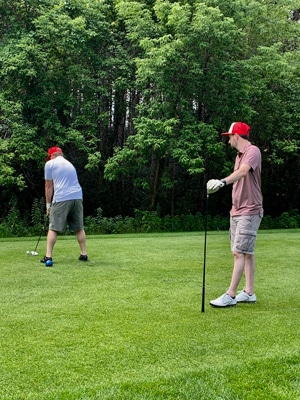 Attorney Ryan Muir waits for his colleague John Foss to tee off at a charity golf tournament benefitting Special Olympics.
