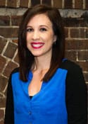 Paralegal Jana Kodesh, wearing a blue blouse and red lipstick, smiles and stands in front of a brick wall.